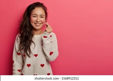 Romantic Chinese woman shows korean heart sign with two fingers crossed, smiles joyfully and confesses in love, expresses affection, wears sweater with heart print, isolated on pink studio wall