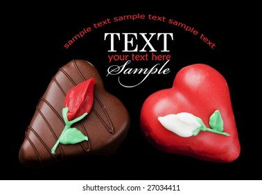 Romantic chocolate and red heart shaped petits fours (small cakes) on a field of black with sample text
