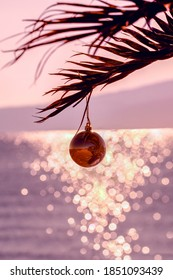 Romantic Christmas background. Palm tree with Christmas ball. Blurred sea and bokeh in background. Christmas greeting card. New Year holiday in warm countries. Pink toning. Vertical. Copy space