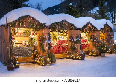 romantic christmas market in Bavaria with illuminated and decorated wooden shops in snow