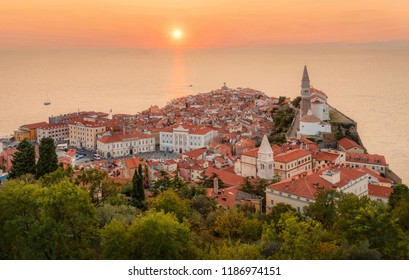 Romantic colorful sunset over picturesque old town Piran with sun on the background, Slovenia. Scenic panoramic view.