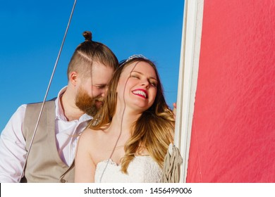 romantic communication of a young couple just married standing on a sailboat at the mast to a scarlet sail