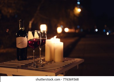 Romantic composition with burning candles and wine on table outdoors at night