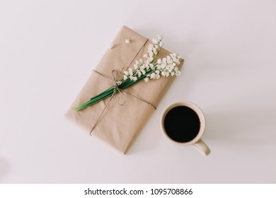 Romantic composition of a cup of coffee, book and flowers on white background. Flat lay, top view, spring concept