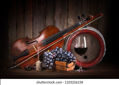 Romantic composition with red grape, wine, violin and barrel