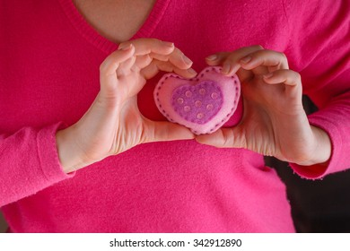 Romantic concept. Female in pink holding soft heart symbol