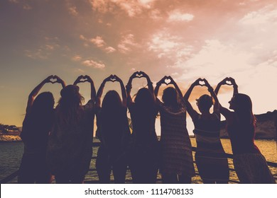 romantic concept for girls doing hearts with hands all together in relationship and friendship in front of a beautiful sunset and the ocean. golden tones for sweet image of group of people outdoor