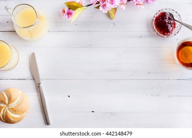 Romantic continental or rural breakfast. Bread, jam, butter, tea and flowers on a rustic white wooden table from above. Countryside weekend concept. Background layout with space for copy.