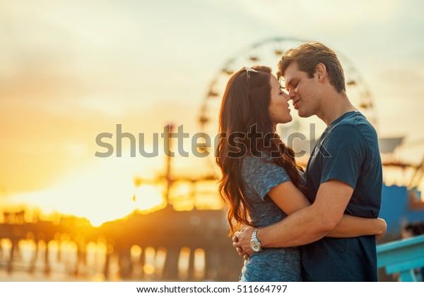 夕暮れ時にキスをしようとしているロマンチックな夫婦