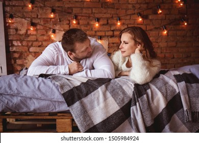 Romantic couple in bed against a brick wall