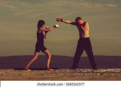 Romantic couple of boxers fighting for love on blue sky. Happy pretty girl or cute woman boxing with handsome man in gloves on sunny, summer day on nature. Sport, energy and competition