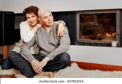 Romantic couple of brunette woman and bald headed man sitting on the fur carpet near the fireplace. Fire in the fireplace is burning.