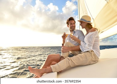 Romantic couple cheering on sailboat at sunset