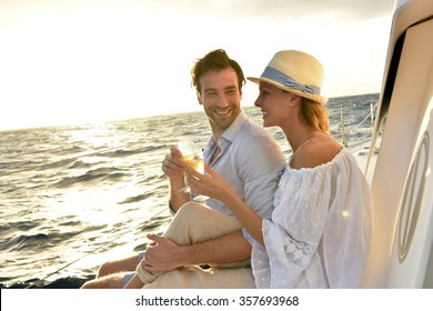Romantic couple cheering on sailboat at sunset