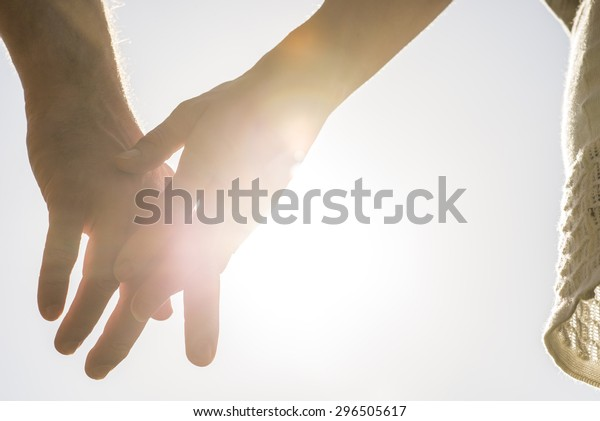 Romantic couple with clasped hands backlit by a bright evening sun in a closeup conceptual image of love, commitment and friendship.
