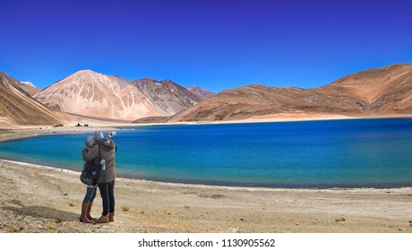 Romantic couple click selfie near scenic Pangong lake Ladakh India.