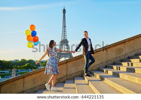 Romantic couple with colorful balloons near the Eiffel tower in Paris, France, walking up the stairs