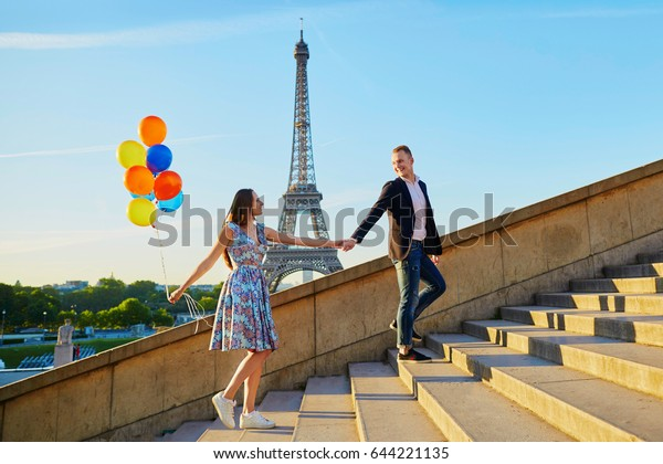 フランス、パリのエッフェル塔の近くに色とりどりの風船を持つロマンチックな夫婦が階段を上がる