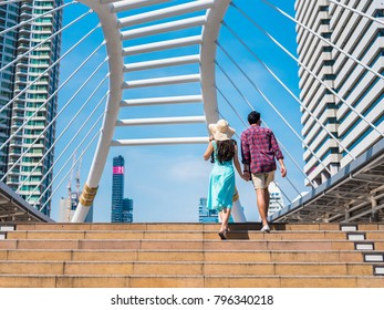 Romantic couple with colorful sky walking up the stairs in the city, Bangkok, Thailand Traveler couple in love walking in summer and holding each other hand
