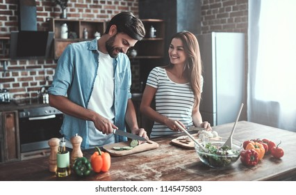 Romantic couple is cooking on kitchen. Handsome man and attractive young woman are having fun together while making salad. Healthy lifestyle concept.