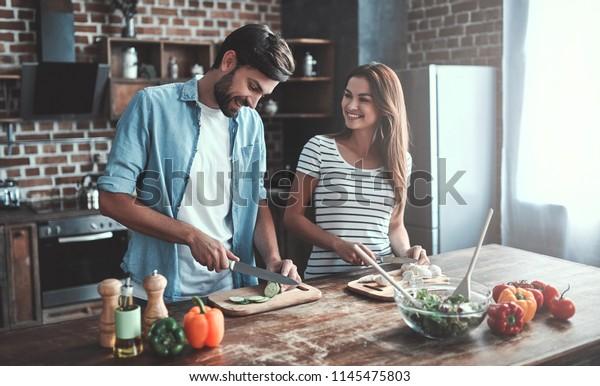 ロマンチックな夫婦は台所で料理をしている。ハンサムな男性と魅力的な若い女性がサラダを作りながら一緒に楽しんでいる。健康的なライフスタイルのコンセプト。