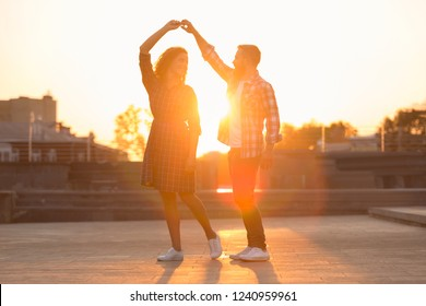 Romantic couple dancing and spending time together againt sunset in city