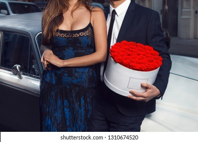 Romantic couple date. Man and woman with rose flowers wearing suit and dress standing near luxury car in the city.
