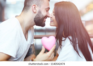 Romantic couple dating in cafe and holding presents