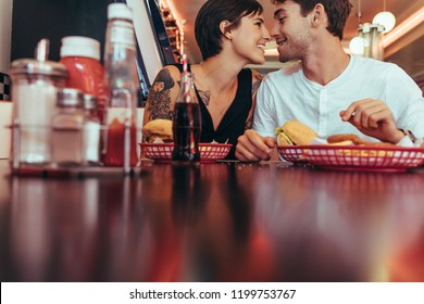 Romantic couple at a diner sharing a french fry holding it in their teeth together and looking at each other. Happy couple dining at a restaurant with food on the table.