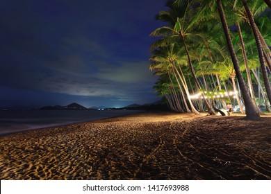 Romantic couple dining under palms, evening under lights, Palm Cove, Cairns Region, Queensland, Australia