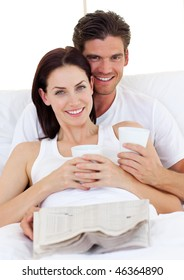 Romantic couple drinking coffee and reading newspaper