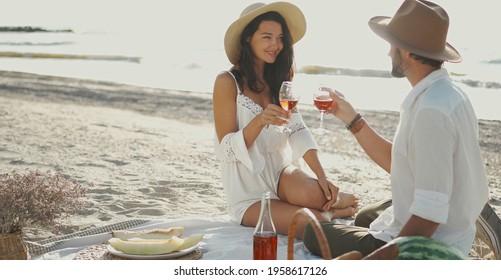 romantic couple drinking wine and enjoying picnic at beach, celebration anniversary relationships