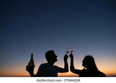 romantic couple drinking wine at sunset