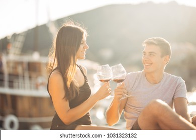 Romantic couple drinking wine at sunset.Romance.Two people having a romantic evening with a glass of wine near the sea.Cruise ship vacation.Luxury class.Sailing and nautical tourism