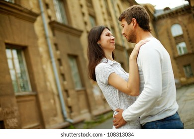 Romantic couple embracing each other in old urban surroundings