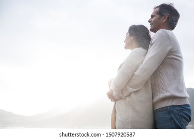 Romantic couple embracing each other on beach during winter