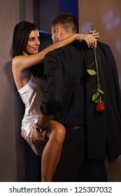 Romantic couple embracing at home, woman in silk nighty holding rose.