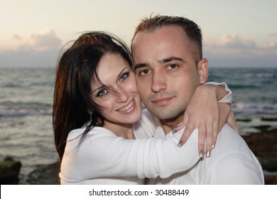 Romantic couple embracing at seaside on sunset