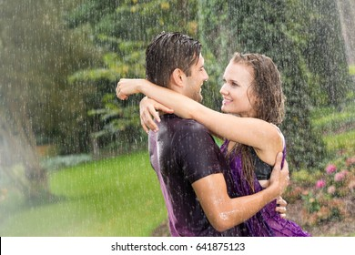Romantic couple embracing in the summer rain