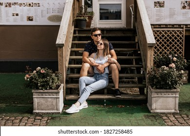 Romantic couple in embrance look away on building background. Happy man and woman are sitting on wood stairs