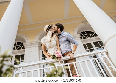 Romantic couple in embrance on white balcony. Stylish couple are kissing