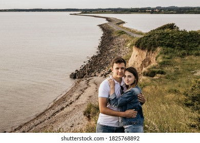 Romantic couple in embrance stand on the beach with mountains. Travel vacation lifestyle concept