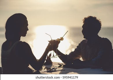 Romantic couple enjoy sunset in restaurant on the beach drinking cocktails