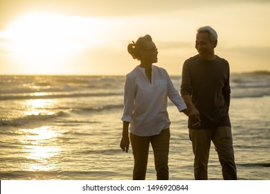 Romantic couple Enjoying senior walking travel on beach at sunset.