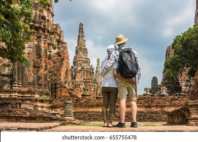 Romantic couple, European and Asian, embracing each other at old temple ruins. Foreign tourists go sightseeing in Ayutthaya Historical Park, Thailand, Southeast Asia.
