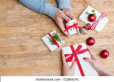 Romantic couple exchanges holiday Christmas gifts on a wooden table with Christmas decorations with room for copy