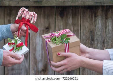 Romantic couple exchanges holiday Christmas gifts in a rustic setting