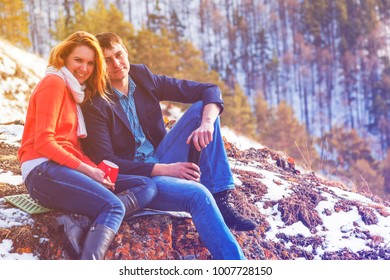 Romantic couple guy and girl on a walk in the woods in winter