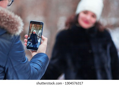 Romantic couple, the guy photographs the girl on the smartphone on the background of beautiful nature in winter