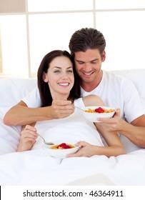 Romantic couple having breakfast lying in the bed